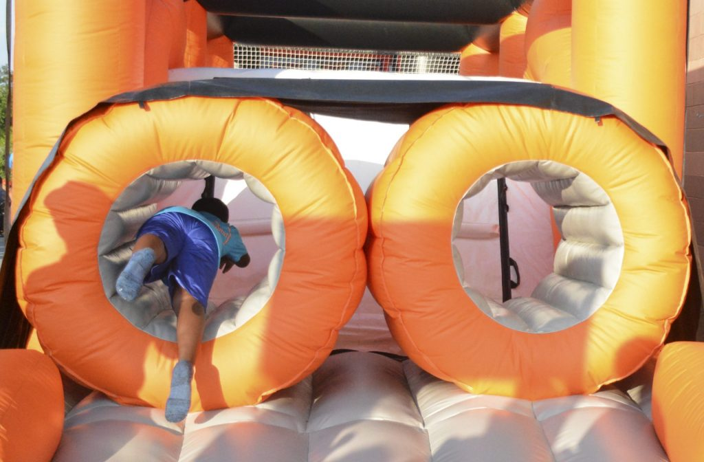 A young Ducks fan jumps through an obstacle course at Bethpage Ballpark on Wednesday, July 24, 2019. A kids zone was set up at the ballpark for family fun. Photo by Lily McInerney.