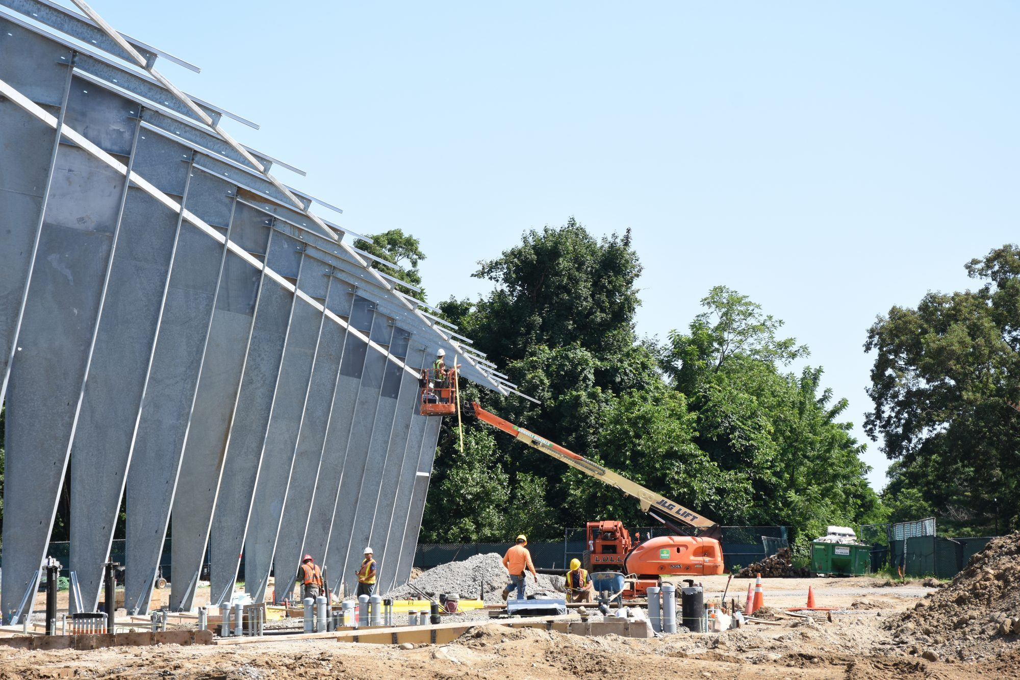 Construction workers work on a new indoor practice facility on Stony Brook University's campus on Thursday, July 25, 2019. The facility is designed for outdoor sports to be able to continue practicing even in inclement weather, according to Associate Athletics Director Adam McLeod. The facility is due to be complete in December 2019. (Photo by Kiana Wright)
