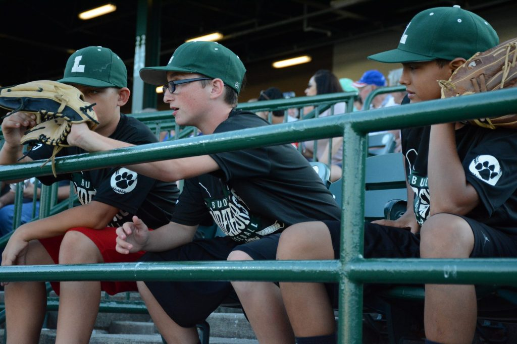 Brandon Eller,11, Devin Barnes,11, Zach Commike, 11, hope to catch a foul ball during the game. All three boys play baseball on the Lindernhurst team. Photo by Julia Heming,